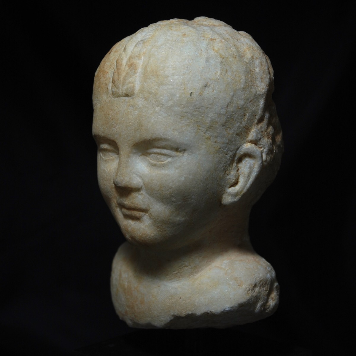 Roman marble head of girl with braided hair left
